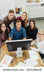 Motivated young business team grouped together at a desktop computer looking up at the camera with happy friendly smiles