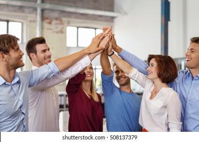 Motivado jovem equipe de negócios prometendo apoio levantando as mãos em uma pirâmide com sorrisos entusiasmados felizes