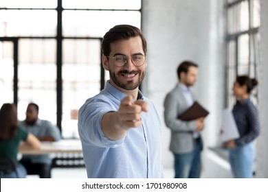 Motivated young Caucasian businessman point at screen welcome new employee or intern at office, happy millennial male boss or CEO offer suggest internship or employment, recruitment concept