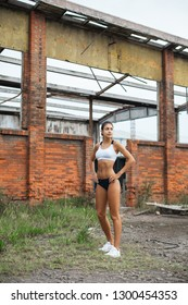 Motivated young female athlete taking a break during outdoor running workout at abandoned industrial ruins. Beautiful fit runner.