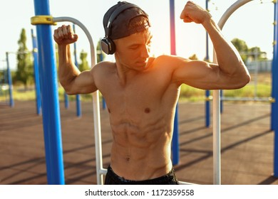 Motivated young male working out on sports ground outdoors. Handsome sportsman  with headphone on head listening the music. Shirtless male model exercising outside. People and sport