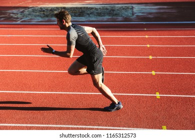 Motivated young sportsman running at the stadium