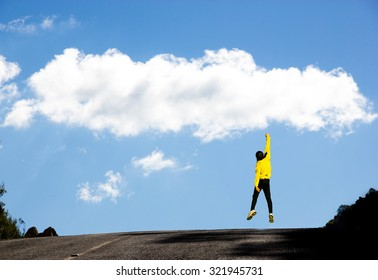 Motivated Young Traveler Man jumping with one Arm Touching the Skies