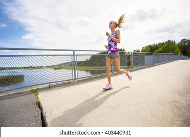 Motivated young woman running fast on bridge over a lake