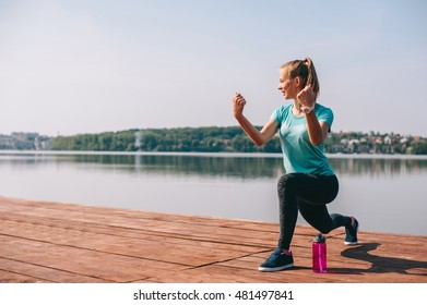 motivating girl performs exercises on the dock overlooking the lake