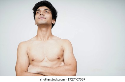 Motivating and smart. Portrait of handsome shirtless young indian boy looking upwards while standing against white background