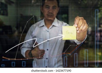"""Motivation, Aim, Traget and Goal Concept. Businessman holding sticky note with """"goal"""" word and graph report on glass window."""