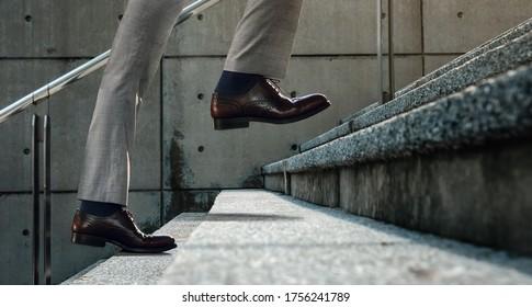 Motivation und anspruchsvolles Konzept. Schritte in Richtung Erfolg. Niedere Sektion Geschäftsmann Auf Treppe steigen