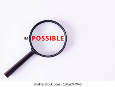 """Motivation concept. An enlarged fragment of expression in the lens of a magnifying glass with text """"POSSIBLE""""."""