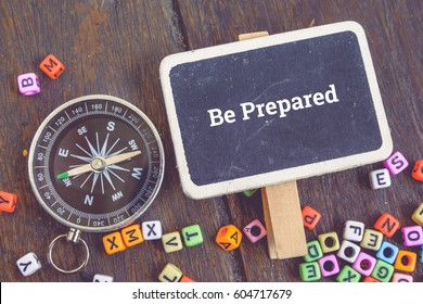 Motivation concept image,word BE PREPARED over top view flat lay wooden signage and compass on wooden background.selective focus shot