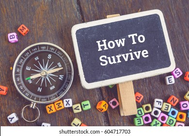 Motivation concept image,word HOW TO SURVIVE over top view flat lay wooden signage and compass on wooden background.selective focus shot