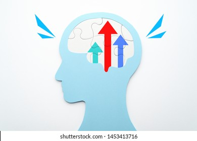 Motivation and improvement concept. Three growth arrows in brain. Head silhouette and brain shaped puzzle pieces on white background.