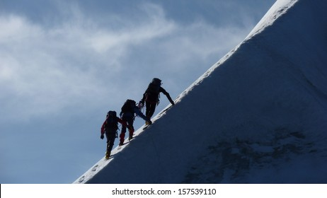 Motivation, Teamwork and Leadership - Rope team climbing steep icy mountain ridge