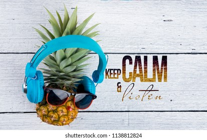 d002bb53db8 Motivation text and Cute ripe pineapple with sunglasses and headphone  listens to music on white wooden