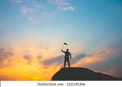 Motivation for trying to succeed in business, Silhouette of man on mountain top over sky and sun light background,business, success, leadership, achievement and people concept