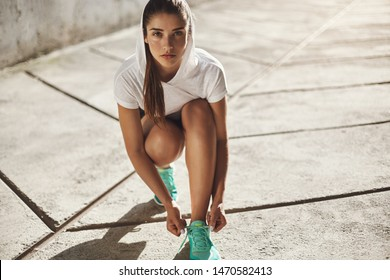 Motivation, urban fitness and running concept. Determined alluring young fit female workout outdoors, kneel to tie shoelaces on sneakers, look camera self-assured, prepare morning jogging