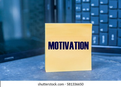 MOTIVATION word on blank note on wooden table over blurry laptop as a background