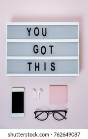 Motivational board, phone and stationery on pink table. Business concept. Top view, flat lay