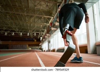 Motivational image of young amputee athlete on start position on running track in modern indoor stadium, focus on artificial foot, copy space