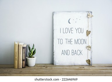 motivational inspirational poster quote LOVE YOU TO THE MOON AND BACK. Room decoration american or scandinavian style  with books, succulent in the pot and heart shaped garland.