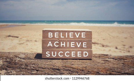 Motivational and inspirational quote - 'Believe, achieve, succeed' written on wooden blocks. Vintage styled background.