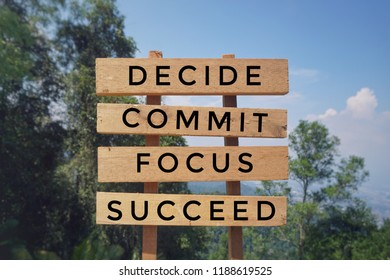 Motivational and inspirational quote - 'DECIDE, COMMIT, FOCUS, SUCCEED' written on wooden signage. Vintage styled background.