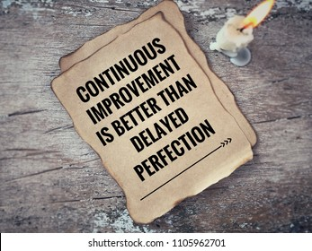 Motivational and inspirational quote - 'Continuous improvement is better than delayed perfection' on a piece of paper. With blurred vintage styled background.