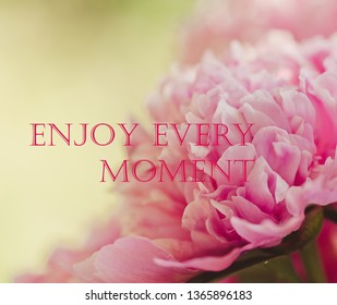 Motivational & inspirational quote with phrase Enjoy Every Moment with beautiful flowers baclground