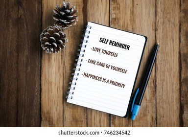 Motivational and inspirational wordings - 'Self reminder: love yourself, take care of yourself, happiness is a priority on a notebook. With blurred styled background of wooden table.