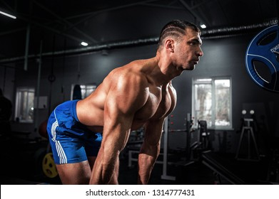 Motivational portrait of a handsome muscular brutal European man with a bare chest working out with dumbbells in a modern gym