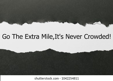 Motivational quote Go The Extra Mile It's Never Crowded appearing behind torn paper.