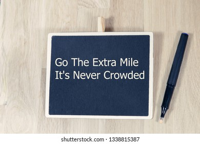 Motivational quote Go The Extra Mile It's Never Crowded with chalkboard on a wooden table with pen. - Image