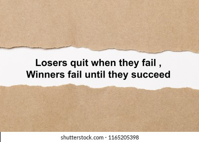 Motivational quote Losers Quit When They Fail Winners Fail Until They Succeed appearing behind paper.