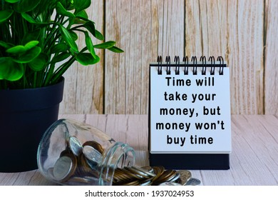 Motivational quote on paper stand and blurred glass jars with multicurrency coins on wooden desk