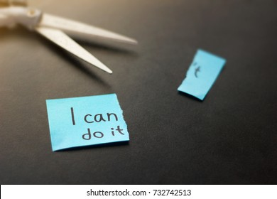 Motivational quote on sticky paper with scissors on dark background. No excuses, i can do it.
