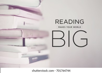 Motivational quote poster Reading makes your world big, sans serif typography on low contrast and blurred photography of a book stack. Relaxing and modern design for positive thinking and happiness.