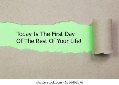 Motivational quote Today Is The First Day Of The Rest Of Your Life appearing behind torn paper.