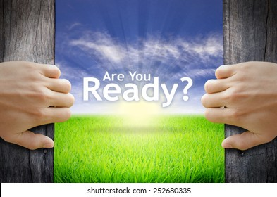 "Motivational quotes ""Are you Ready"" . Hands opening a wooden door then found a texts floating among new world as green grass field, Blue sky and the Sunrise."