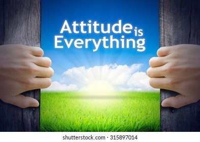 """Motivational quotes """"Attitude is Everything"""" . Hands opening a wooden door then found a texts floating among new world as green grass field, Blue sky and the Sunrise."""