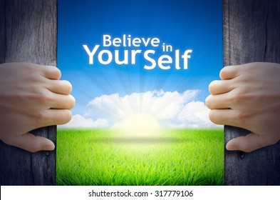 """Motivational quotes """"Believe in your self"""". Hands opening a wooden door then found a texts floating among new world as green grass field, Blue sky and the Sunrise."""