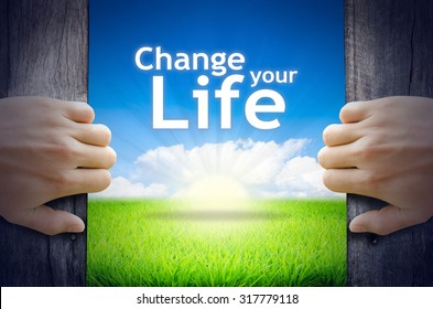 """Motivational quotes """"Change your Life"""". Hands opening a wooden door then found a texts floating among new world as green grass field, Blue sky and the Sunrise."""