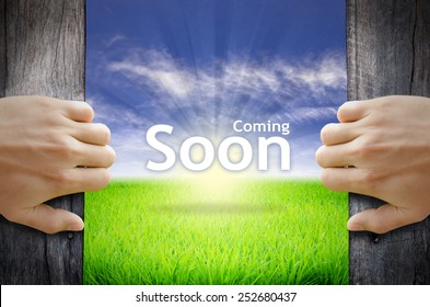 "Motivational quotes ""Coming Soon"" . Hands opening a wooden door then found a texts floating among new world as green grass field, Blue sky and the Sunrise."