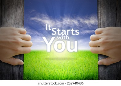 """Motivational quotes """"It starts with You"""" . Hands opening a wooden door then found a texts floating among new world as green grass field, Blue sky and the Sunrise."""