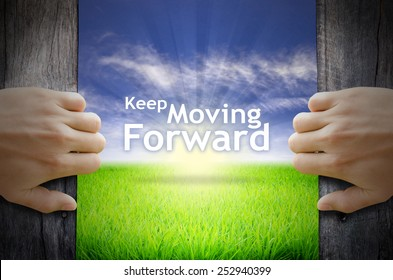 """Motivational quotes """"Keep Moving Forward"""" . Hands opening a wooden door then found a texts floating among new world as green grass field, Blue sky and the Sunrise."""