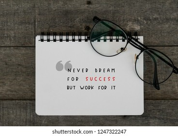 Motivational quotes, NEVER DREAM FOR SUCCESS BUT WORK FOR IT, notebook and eye glass over the wooden table
