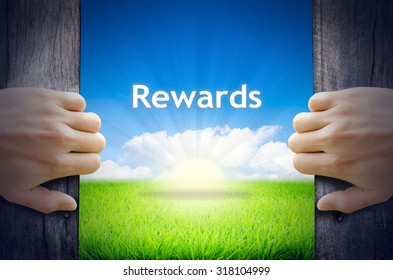 """Motivational quotes """"Rewards"""". Hands opening a wooden door then found a texts floating among new world as green grass field, Blue sky and the Sunrise."""
