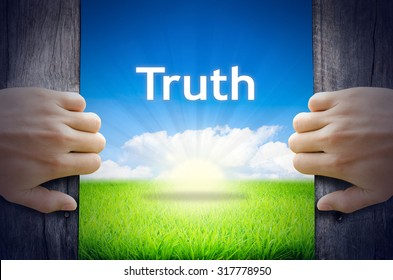 """Motivational quotes """"Truth"""". Hands opening a wooden door then found a texts floating among new world as green grass field, Blue sky and the Sunrise."""