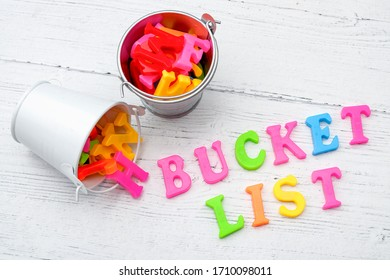 """Motivational resolution, ambitious wish and achieve important goals concept with buckets of letters and the text """"bucket list"""" on white wood background"""