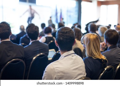 Motivational speaker giving a talk in conference hall at business event. Audience at the conference hall. Business and Entrepreneurship concept. Focus on unrecognizable people in audience.
