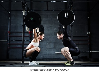 Motivational wiade shot of young man and woman holding huge heavy barbells overhead looking at each other